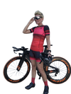 Lifestyle picture of a female triathlete wearing a red triathlon outfit with her bike