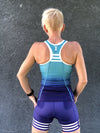 Rear view of a female athlete wearing a blue triathlon tank top