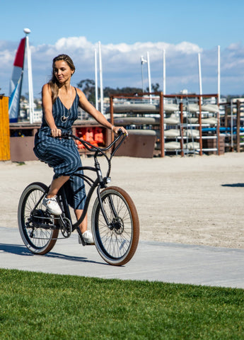 woman bicycling along the oceanfront in a pinstripe jumpsuit in the summer