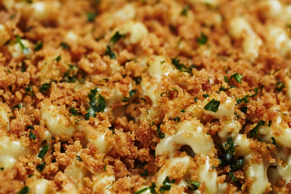 Close up image of vegan mac and cheese covered in toasted breadcrumbs with chopped parsley