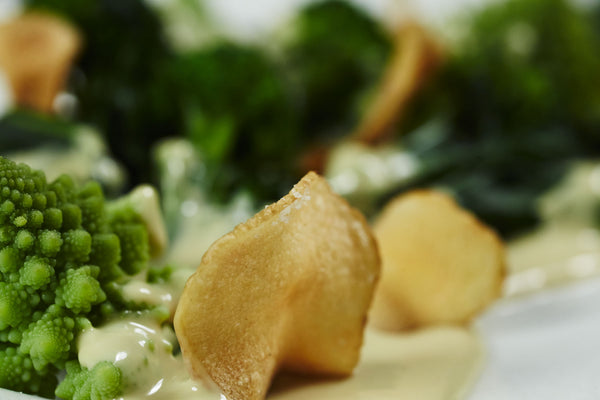 Close up of a fresh made sunchoke chip in front of blanched romanesco and broccolini and covered in Kashoo Queso