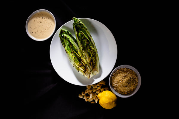 Recipe for grilled romaine lettuce, plant-based caesar dressing, parmesan crumble, croutons, lemon ready to be plated