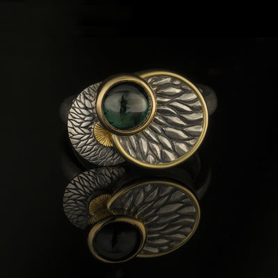 silver and gold ring with green tourmaline and leaf motiff