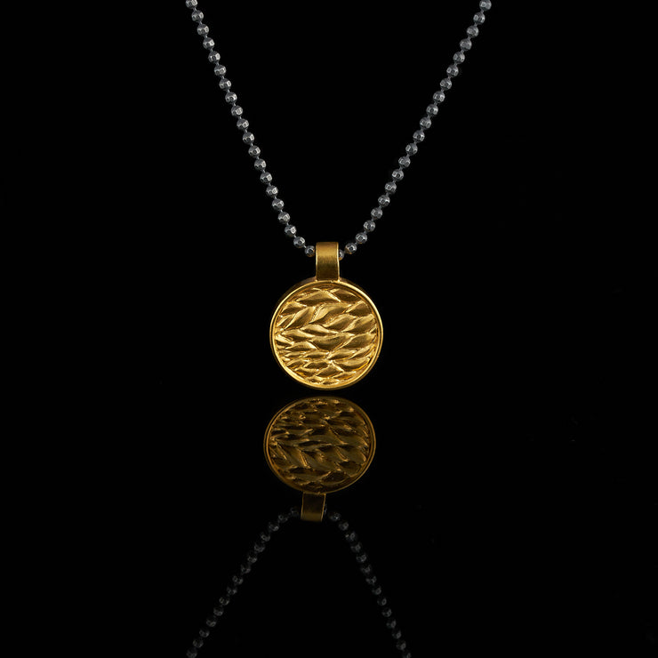 gold plated medal with leaf pattern, black and gold pendant