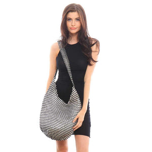 "alt=""boho crossbody bag black and silver color worn by woman in black dress"""
