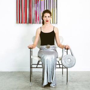 "alt=""silver metal purse with model seated in chair, Escama Studio"""