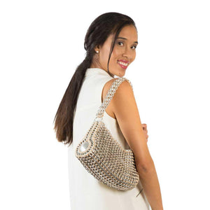 "alt=""silver shoulder bag cylinder purse made of pop tabs by Escama Studio worn by woman in cream colored top"""