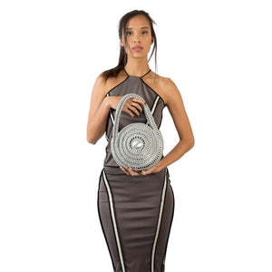 "alt=""round silver metal purse held by woman in dress, Escama Studio Spiral Bag"""