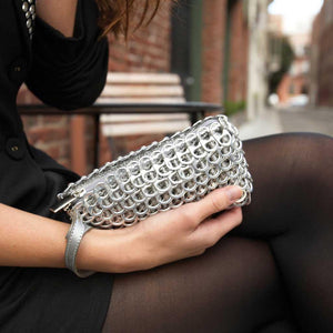 "alt=""silver clutch bag with wrist strap held by sitting woman, Puff recycled purse by Escama Studio"""