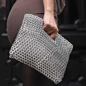 "alt=""silver clutch purse with cut out handle held by woman, Leda bag by Escama Studio"""