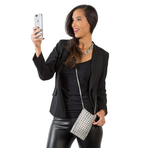 "alt=""silver crossbody phone bag carried by woman in black jacket and black leather pants"""