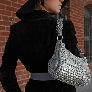 "alt=""silver cylinder purse shoulder bag worn by woman in black coat and black hat, Danubia bag by Escama Studio"""