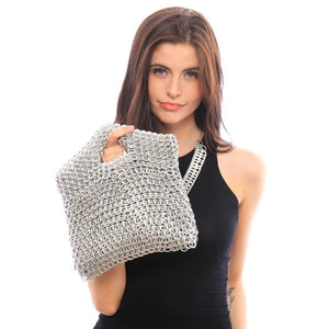 "alt=""silver clutch with cut out handle held by young woman in black dress,  Leda eco fashion purse by escama studio"""
