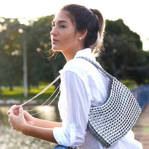 "alt=""silver purse worn by girl in white shirt looking over water at sunset, ethical fashion by Escama Studio"""