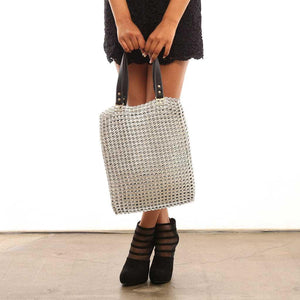 "alt=""silver tote with black leather straps held by woman in black dress and black heels, Luci silver zipper tote bag by Escama Studio"""