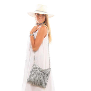 "alt=""silver square clutch with cross body chain, escama leda bag worn by young woman in white dress and white hat"""