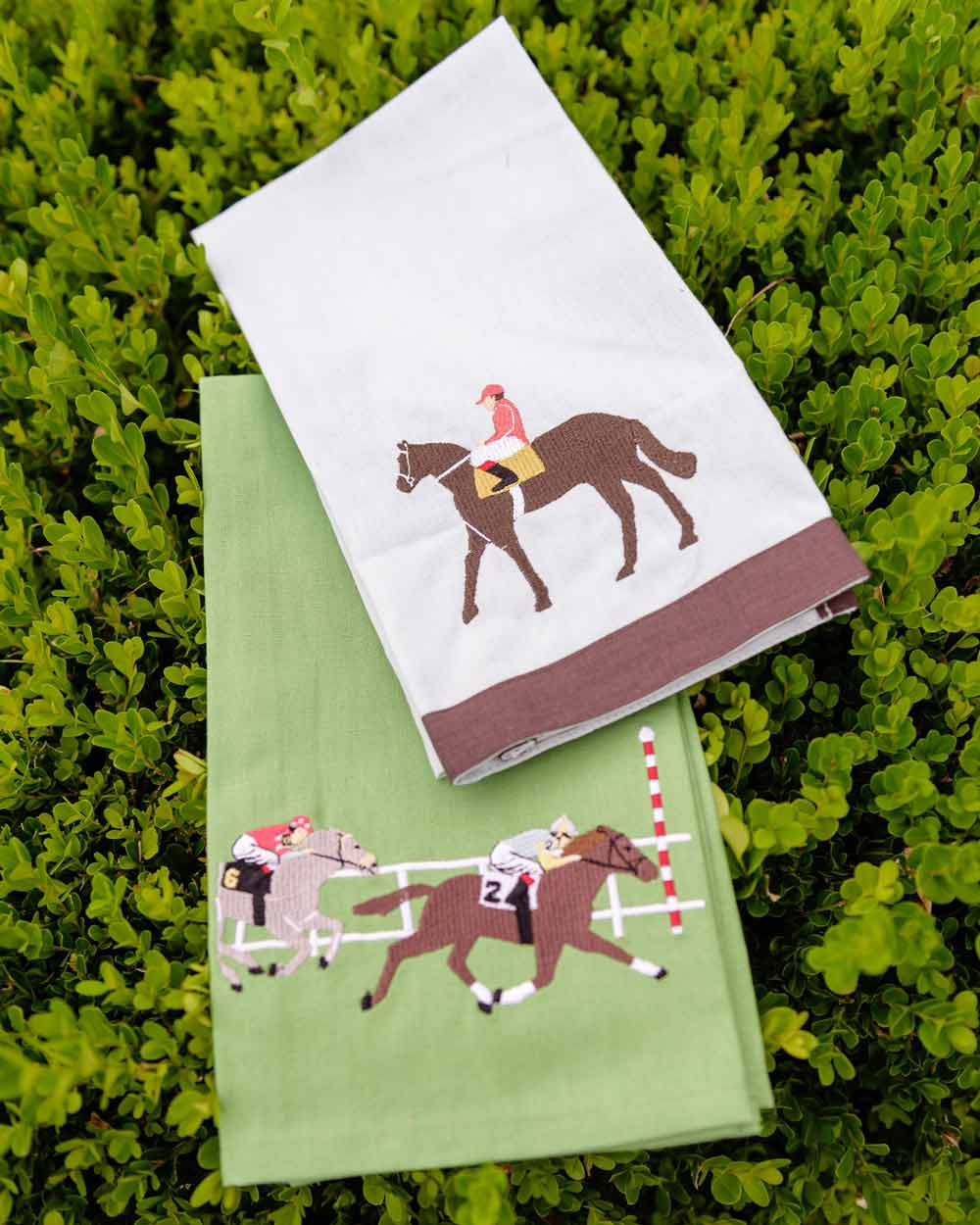 embroidered equestrian towels laying on bush