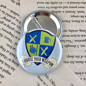 "blue and green creative crest button reading ""choose your weapon"""