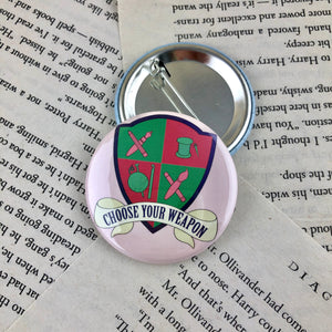 "pink and green creative crest button reading ""choose your weapon"""