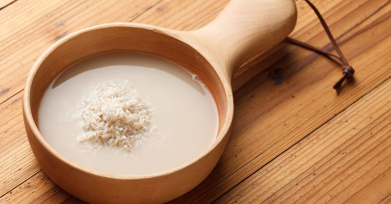 Rice and rice water in a wooden bowl on a wooden table