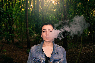A woman vapes in front of a background of trees