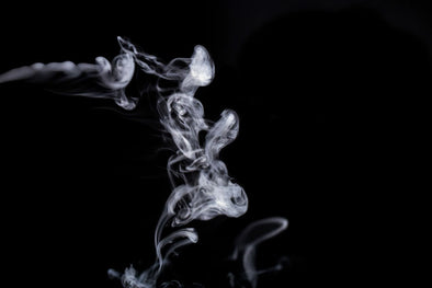 A pale gray wisp of smoke against a black background