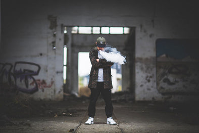 A man in an urban setting exhaling a cloud of vape.
