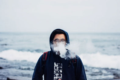 A man vaping on a beach with waves crashing behind him