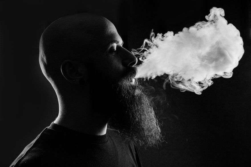 A black and white picture of a man with a beard vaping