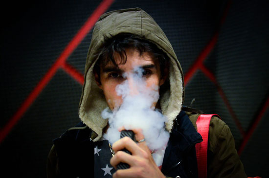 A person in a hooded jacket vaping