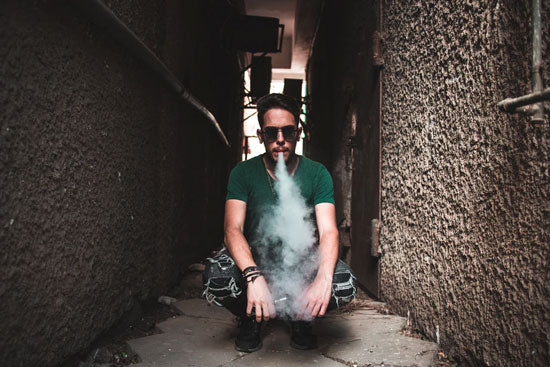 A man in a hallway vaping surrounded by thick clouds