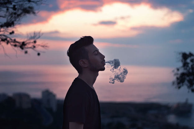 A man exhales vapor as the sky brightens behind him