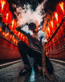 A man squatting while exhaling a cloud of vape