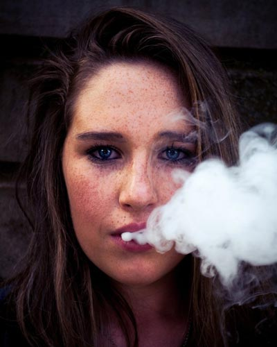 A woman exhaling a cloud of vapor.