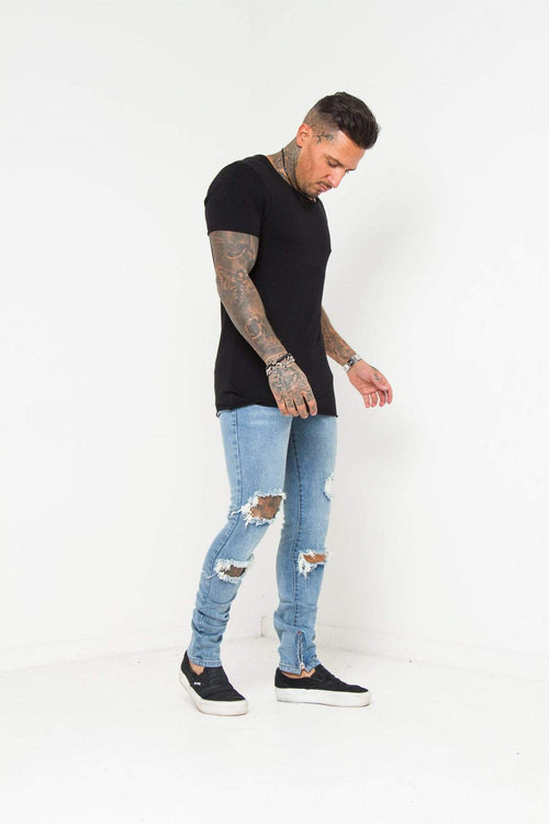 Logan Skinny Stretch Jeans In Light Stonewash With All Over Distressing And Zipped Ankle Hem - Liquor N Poker  Liquor N Poker