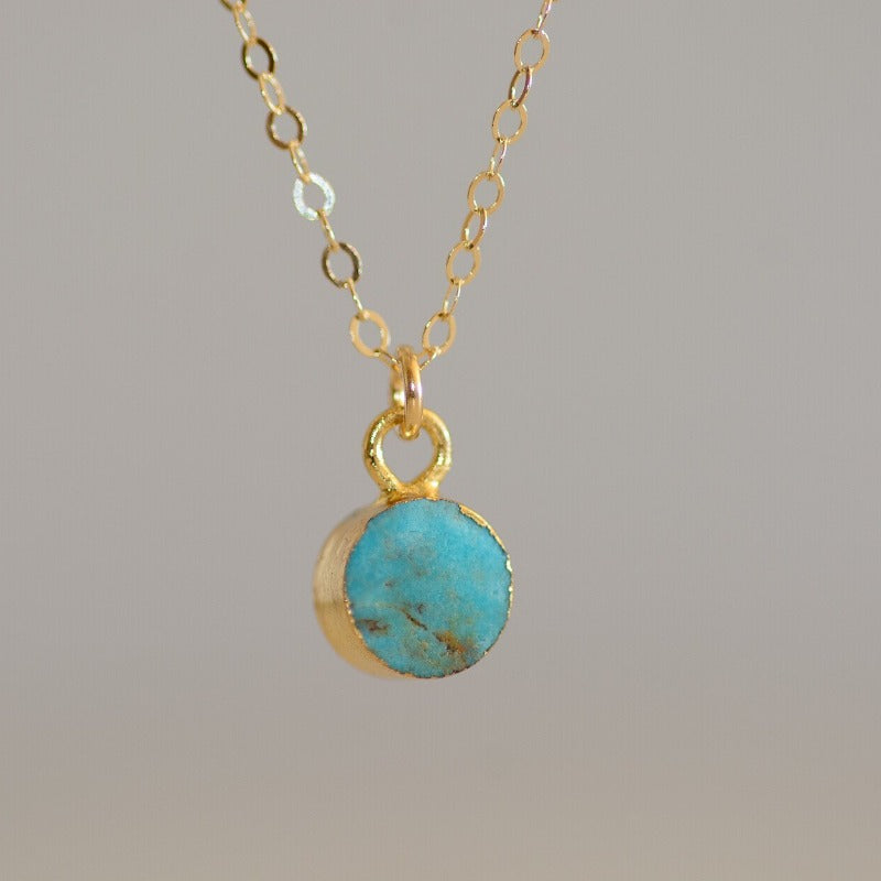 Tiny circular turquoise stone set in gold on dainty gold chain