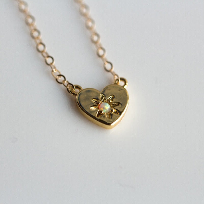 Gold heart charm necklace with a center opal stone