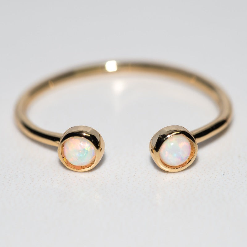 Gold cuff ring with two small round opal stones