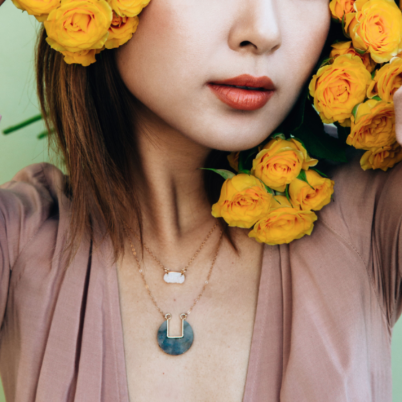 Model wearing blue coin-shaped necklace