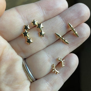 Hand holding mini triple star gold studs, god sunburst earrings and minimal  gold spike barbell posts.