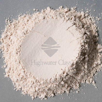 A clump of dry, light pink raw material crushed flat in the center displaying Highwater Clays logo.  Gray background.