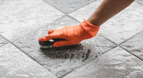 Cleaing tiles with a brush in hand