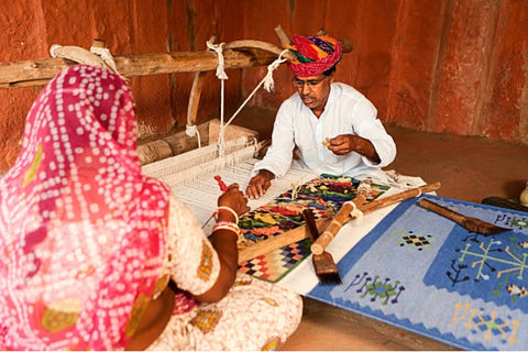 Man and woman weaving a dhurrie rug