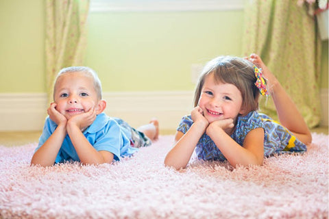 Two kids smiling on shaggy rug
