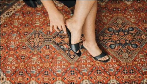 Woman feet and traditional area rug