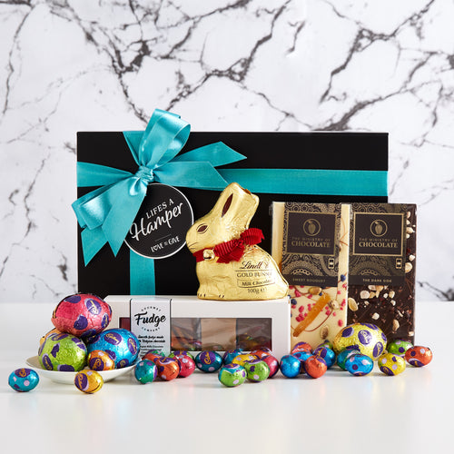 This Easter gift hamper includes a variety of sweet treats perfect for easter. It has a variety of small Cadbury Easter eggs, a Lindt gold bunny, The ministry of chocolate bars and a gift box with an assortment of fudges from the gourmet fudge company.