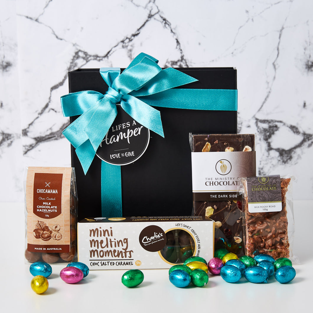 This Easter Chocolate Box comes with Charlie's choc salted caramel mini melting moment. chocolate hazelnuts and The ministry of chocolate chocolate bar and rocky road. This hamper also includes lots of little milk chocolate easter eggs.