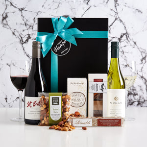 Luxury Wine Duo Gift Hamper is a modern, great tasting food and wine hamper. This Luxury Wine Duo Gift Hamper includes a bottle of Nugan estate Pinot Grigio and a bottle of St Erth Pinot Noir. It comes with a delightful assortment of fudges from the gourmet fudge company as well as some nuts, walnut cracker and some nougat. A popular Christmas Gift Hamper for clients, staff and associates.