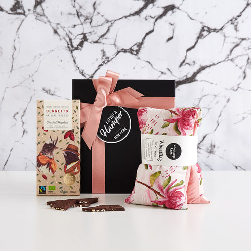 Time Out Gift Hamper comes in a black box with pink ribbon. It's a simple yet stylish gift hamper and includes a wheat bag by wheatbags love and a bennetto natural foods company toasted hazelnut chocolate. This gift it the perfect gift to send a friend to say I'm Thinking of You or R U OK?