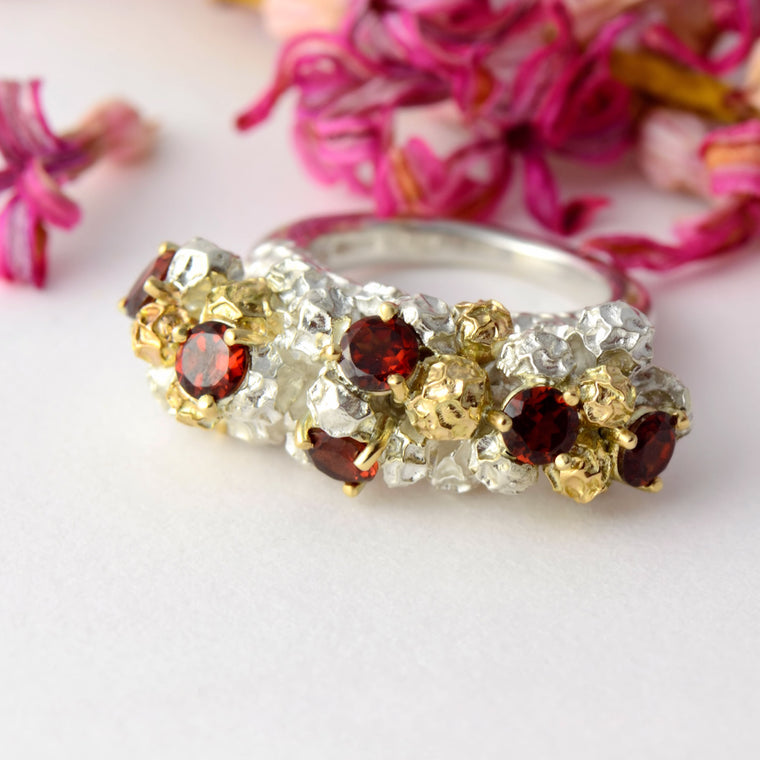 large modern dress ring made in gold, silver and garnets
